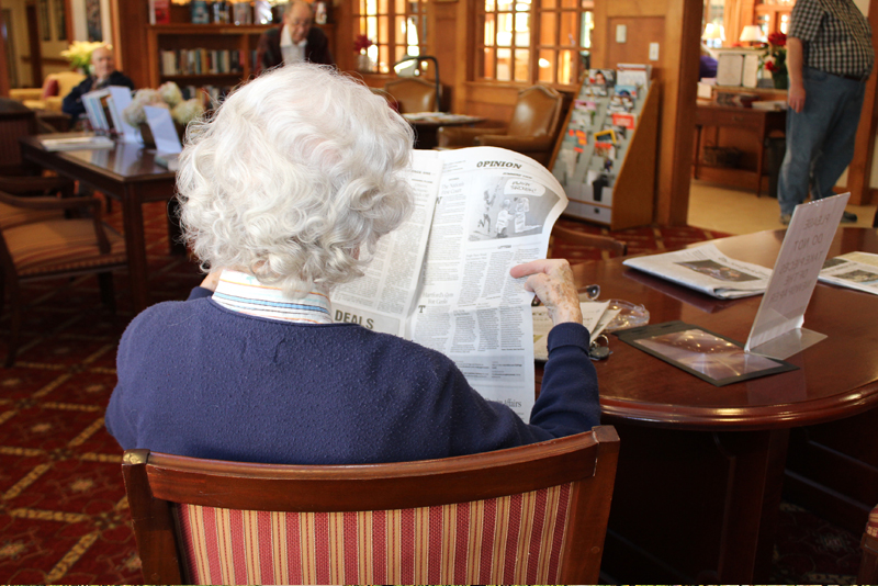 woman reading in the senior living common areas